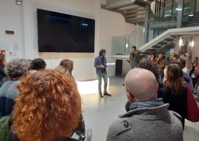 Pubblico che assiste alla presentazione di un evento nei pressi dell'ingresso del Laboratorio